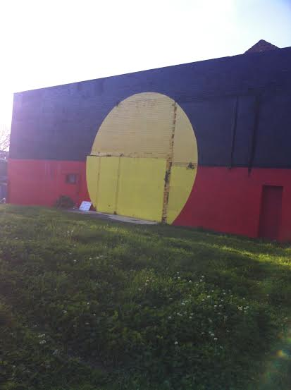 The Australian Aboriginal Flag painted on a wall next to the tent embassy. Another difference from the United States: it is designated as one of the official flags of Australia and is flown alongside the Australian flag.